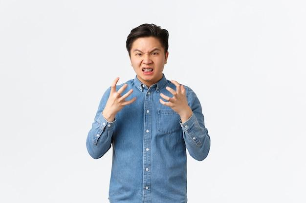 Verontwaardigde agressieve en pissige aziatische man die gefrustreerd en boos de hand schudt, fronsend en grimassend, boos vloekend op iemand, woedend voelend, staande witte achtergrond.