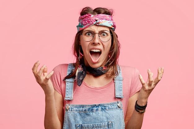 Verontwaardigde boze hippievrouw gebaart met handen, roept woedend, drukt negatieve emoties uit, gekleed in modieuze overall en hoofdband, poseert tegen roze muur