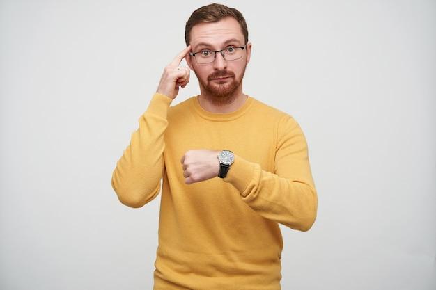 Verontwaardigde jonge brunette bebaarde man in glazen toont zijn polsbandje horloge en houdt wijsvinger op de tempel terwijl hij kijkt met gevouwen lippen, geïsoleerd