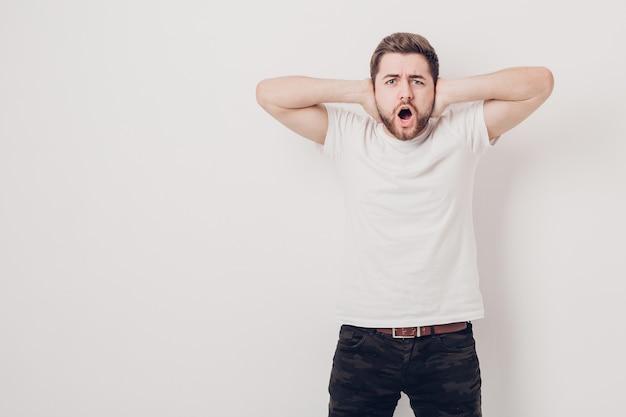 Verontwaardigde jonge man met donker haar en de baard in wit t-shirt schreeuwt voor een witte muur. zacht licht