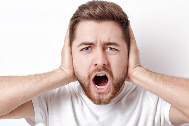 Verontwaardigde jonge man met donker haar en de baard in wit t-shirt schreeuwt voor een witte muur