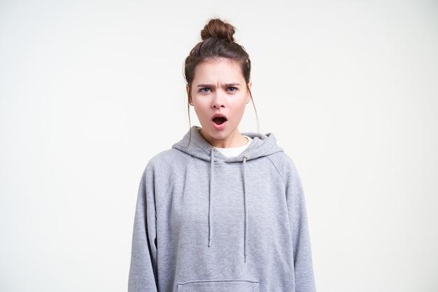 Verontwaardigde jonge mooie brunette vrouw met natuurlijke make-up fronst haar wenkbrauwen terwijl ze wrokkig naar de camera kijkt, staande tegen een witte achtergrond
