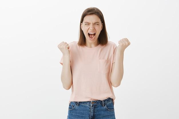 Verontwaardigde jonge vrouw die wordt verraden, agressief schreeuwend van haat en woede