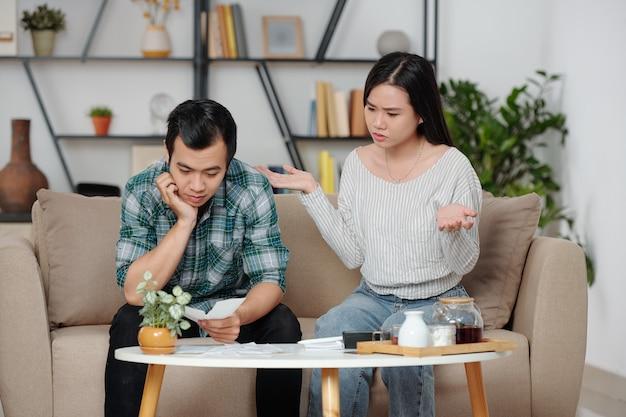 Verontwaardigde jonge vrouw en haar trieste echtgenoot kijken naar stapel rekeningen op de koffietafel voor therm