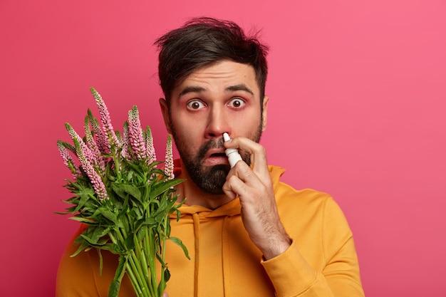 Verontwaardigde man met waterige ogen sproeit neus met druppels, voelt zich ziek vanwege allergie, draagt gele sweater, behandelt seizoensgebonden ziekte, geïsoleerd op roze muur, heeft roodheid rond de ogen