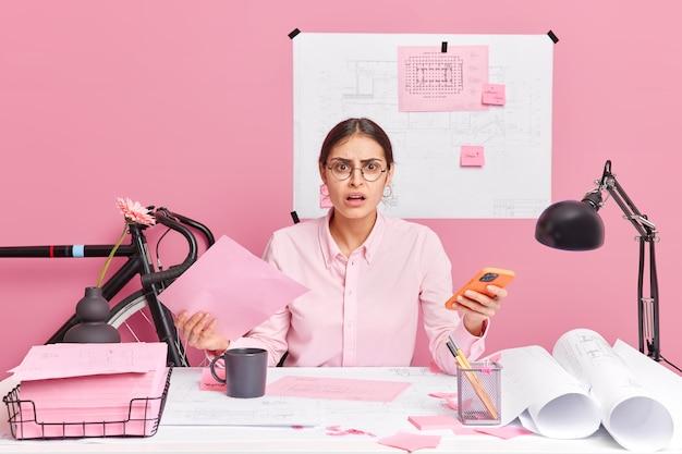 Verontwaardigde ontevreden vrouwelijke kantoormedewerker heeft veel papierwerk voelt zich verward houdt mobiele telefoon probeert ideeën te genereren voor engineeringproject poses in coworking-ruimte maakt schetsen blauwdrukken