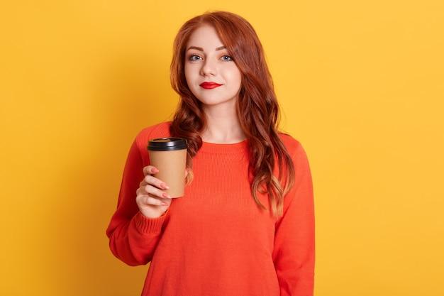 Verontwaardigde vrouw met kalme gezichtsuitdrukking, heeft koffiepauze, houdt papieren beker vast,