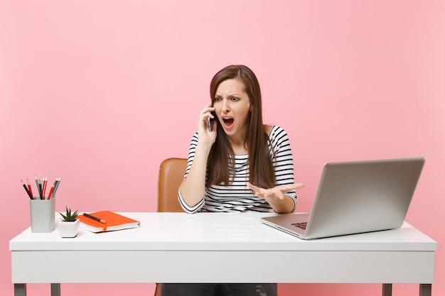 Verontwaardigde vrouw spreidt handen pratend op mobiele telefoon zittend, bezig met project op kantoor met pc-laptop geïsoleerd op pastelroze achtergrond. prestatie zakelijke carrière concept. ruimte kopiëren.