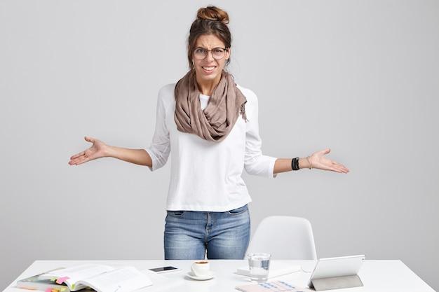 Verontwaardigde vrouwelijke manager gebaart verontwaardigd, heeft veel werk te doen,