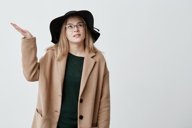 Verontwaardigde vrouwelijke studentengebaren met verontwaardiging in jas en zwarte hoed, staat op straat, weet niet wat ze moet doen vanwege slecht weer. ontevreden en ontevreden blondemeisje dat in verwarring wordt gebracht