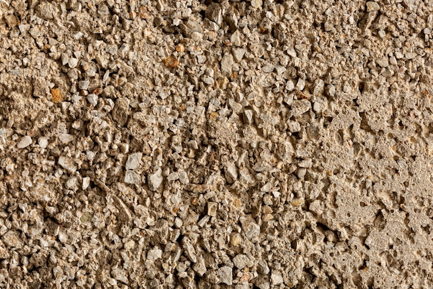Verouderde cementoppervlakte met rotsen en kiezelstenen