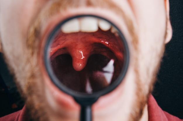 Verouderde keel onder een vergrootglas. portret van een man met een snor close-up.
