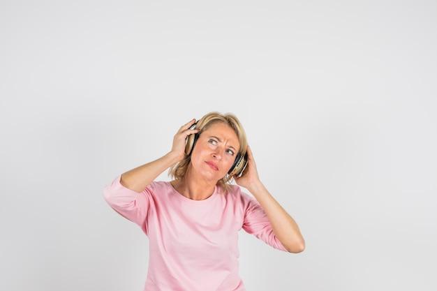 Verouderde peinzende vrouw in roze blouse met hoofdtelefoons