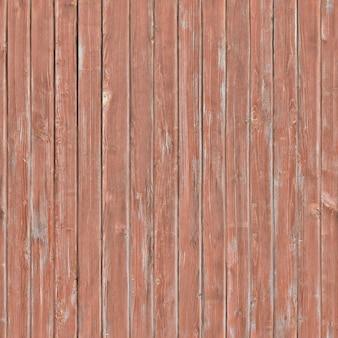 Verouderde schuttingplanken met afbladderende rode verf erop.achtergrond of textuur