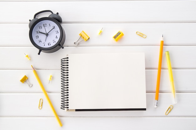 Verouderde witte houten bureautafel met een zwarte vintage wekker, blocnote en gele potloden, platliggend