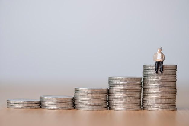 Verouderende samenleving en geld besparen voor pensioen concept, oude man zittend op munten stapelen.