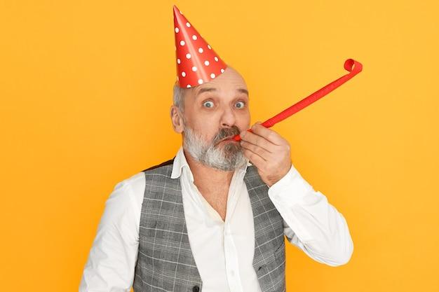 Veroudering, pensionering en feestconcept. studio foto van grappige opgewonden senior man met kaal hoofd en grijze baard, het dragen van elegante kleding en kegel hoed fluitje blazen, verjaardag vieren