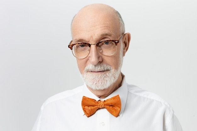 Veroudering, volwassenheid en mensenconcept. foto van serieuze senior man met dikke baard en kaal hoofd fronsende wenkbrauwen, in slecht humeur vanwege hoofdpijn, poseren geïsoleerd op copyspace muur