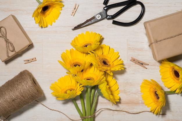 Verpakken van bloemen cadeau over houten achtergrond. bovenaanzicht met kopieerruimte