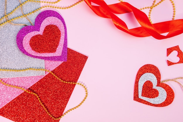 Verpakken van valentijnsdag- of verjaardagscadeaus. valentijnsdag geschenken met een hart van rood papier op een roze ondergrond. bovenaanzicht. roze achtergrond. ruimte voor tekst.