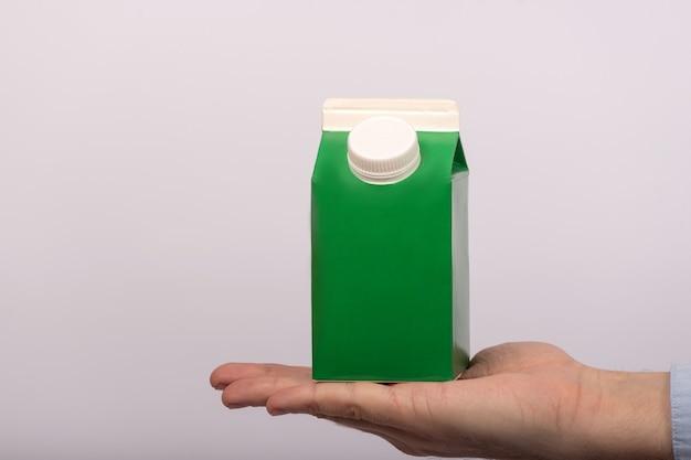 Verpakking kartonnen pack sjabloonproduct. groene kartonnen container met deksel voor melk of sap. bespotten.