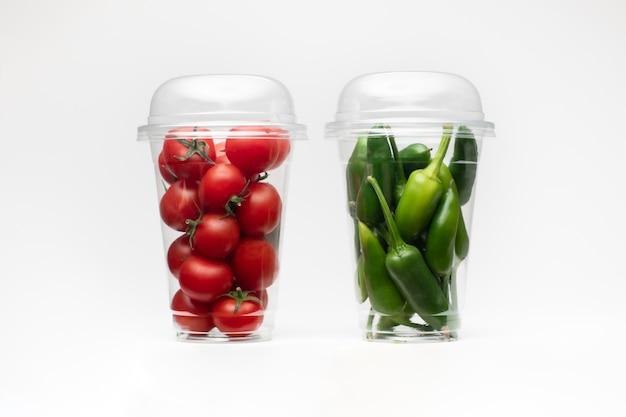 Verpakking met groene paprika en tomaat op witte ruimte. geïsoleerde witte ruimte. tomaten geïsoleerd.
