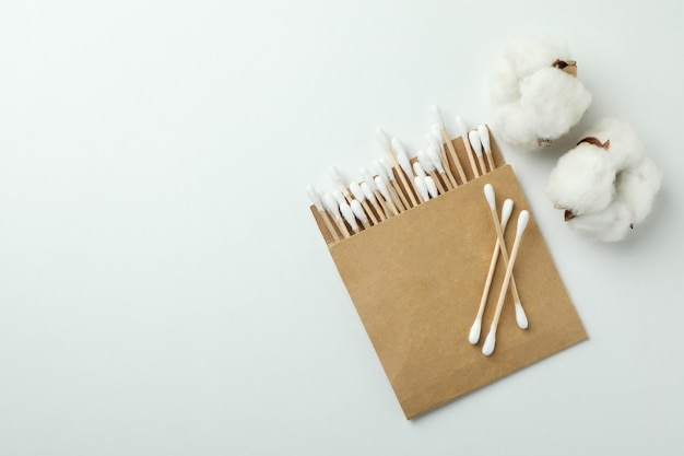 Verpakking met wattenstaafjes en katoen op witte achtergrond