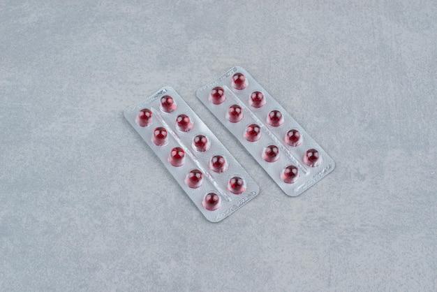 Verpakking ovale rode geneeskundepillen op grijs
