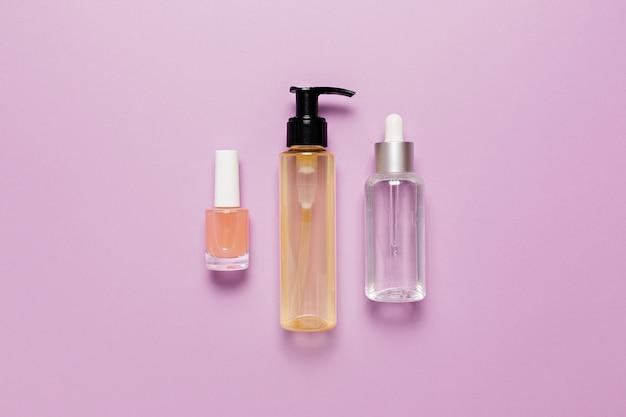 Verpakkingsontwerp voor biologische cosmetica. platliggend, bovenaanzicht helder glazen pompflesje, penseelpotje, vochtinbrengende serumpot op een paarse achtergrond. natuurlijke cosmetica spa