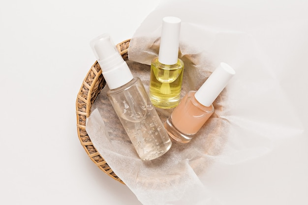 Verpakkingsontwerp voor biologische cosmetica. platliggend, bovenaanzicht helder glazen pompflesje, penseelpotje, vochtinbrengende serumpotje in een papieren mandje op een witte achtergrond. natuurlijke cosmetica spa