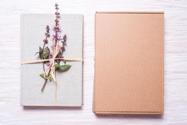 Verpakt boek met bloemen in kartonnen geschenkdoos