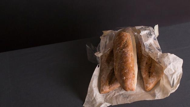 Verpakt brood van broden gewikkeld in papier tegen de achtergrond