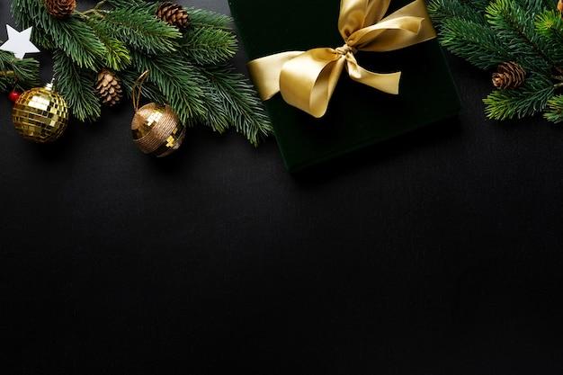 Verpakt cadeau met groene strik en kerstballen op een donkere achtergrond.