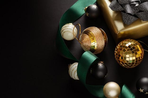 Verpakt cadeau met strik en kerstballen op een donkere achtergrond.