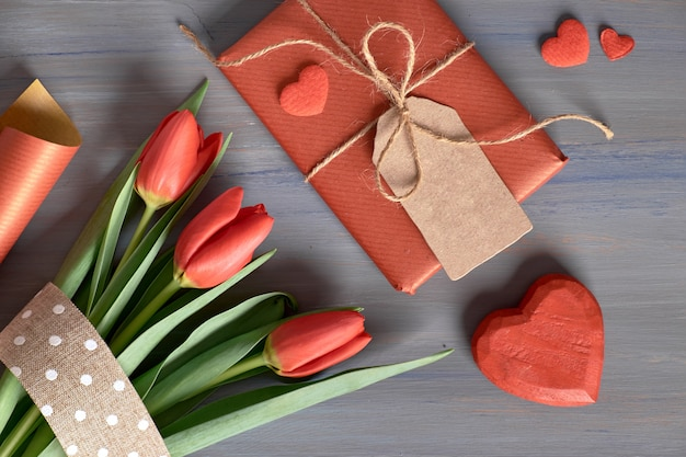 Verpakt cadeau rode tulpen, inpakpapier en decoratieve harten op houten tafel