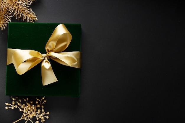 Verpakt gouden geschenk met gouden boog en kerstballen op een donkere achtergrond.