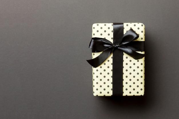 Verpakt kerst- of andere handgemaakte kerstcadeau in zwart lint op papier.