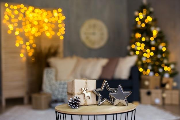 Verpakt kerstcadeau en sterren in ingerichte woonkamer met kerstboom