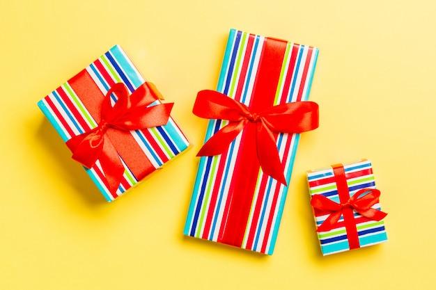 Verpakt kerstcadeau of ander handgemaakt kerstcadeau in papier met rood lint op geel.