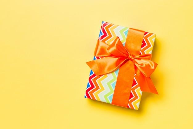 Verpakt kerstcadeau of ander met de hand gemaakt kerstcadeau in papier met oranje lint op geel