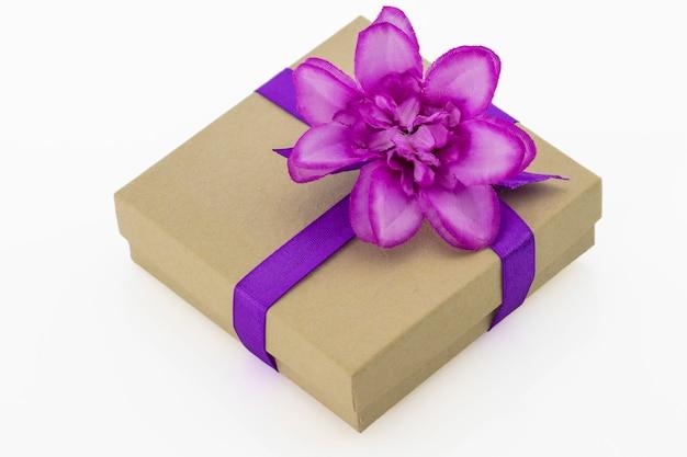 Verpakt vintage geschenkdoos met paarse lint en bloem geïsoleerd