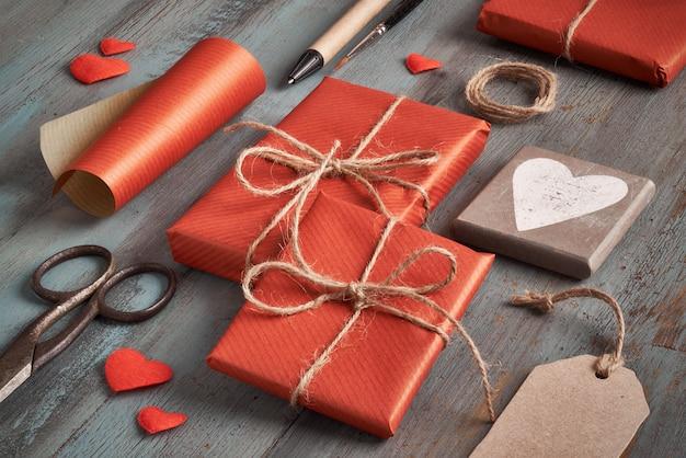 Verpakte cadeaus, papier, koord en etiketten op houten tafel