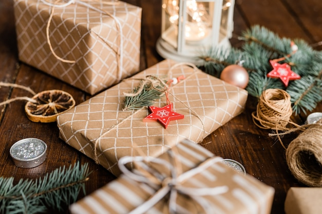 Verpakte geschenkdoos met conifeer en rode ster versiering aan de bovenkant omgeven door draden, kaars en andere dozen