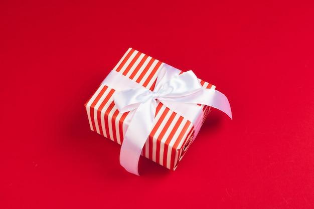 Verpakte geschenkdoos op een rode achtergrond, weergave van bovenaf