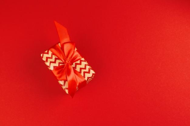 Verpakte geschenkdoos op een rode achtergrondweergave van bovenaf