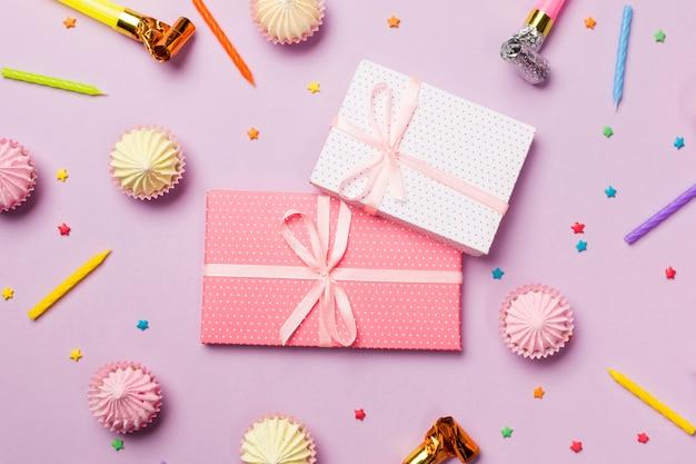 Verpakte geschenkdozen omringd met kaarsen; feest hoorn; hagelslag; geschenkdozen; aalaw op roze achtergrond