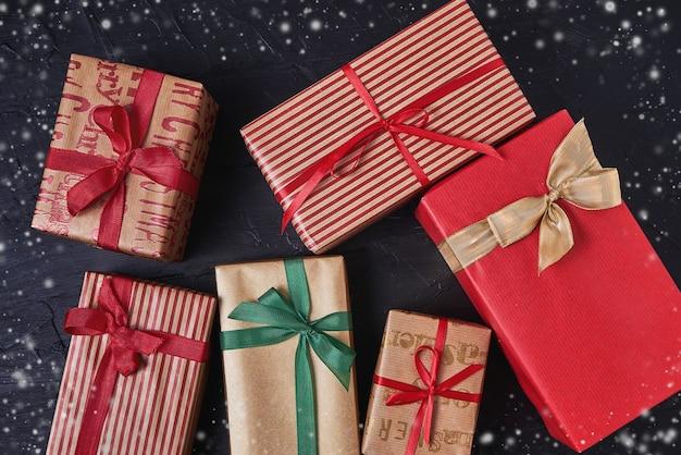 Verpakte geschenkdozen versierd met lint op zwarte houten achtergrond. kopieer de ruimte, bovenaanzicht, sneeuw textuur
