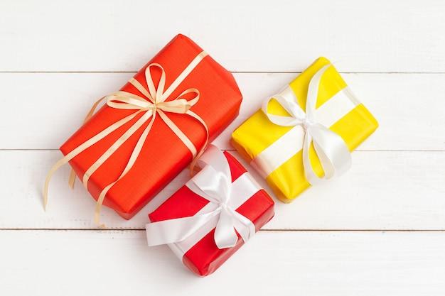 Verpakte geschenken met lint op witte houten bovenaanzicht