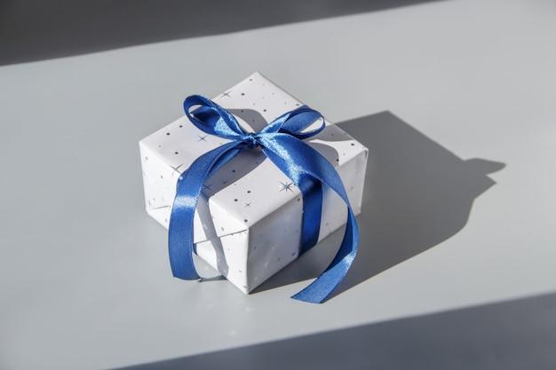 Verpakte grijze geschenkdoos met blauw lint