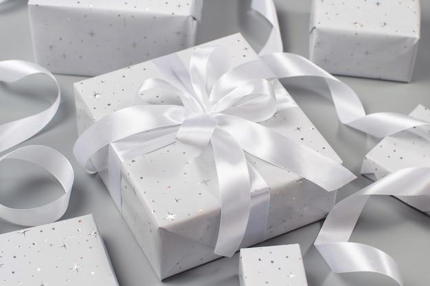 Verpakte grijze geschenkdozen met wit lint op grijs
